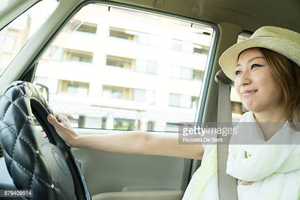 Cheerful Japanese woman driving car wearing