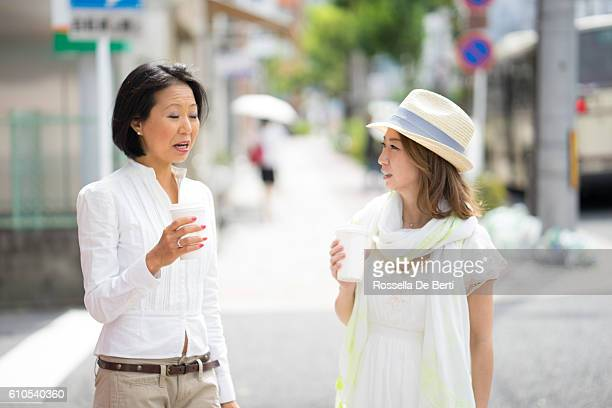 Cheerful Japanese women having a walking meeting, cityscape on background