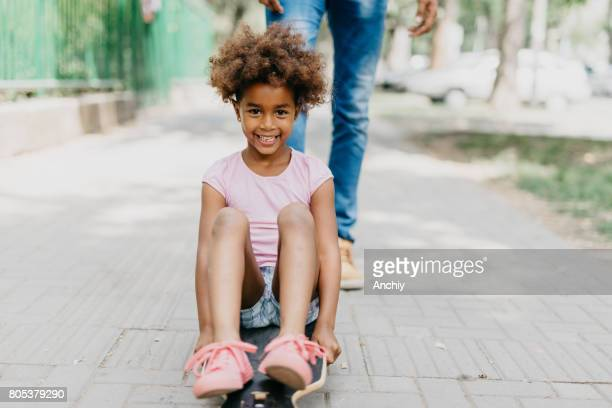 Cheerful kid sitting on the longboard in the park