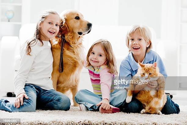 Cheerful kids and their domestic animals at home.