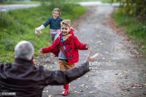 Cheerful kids running towards their grandparent in nature.