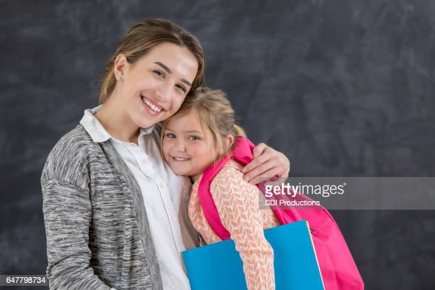 Cheerful kindergarten teacher with young student