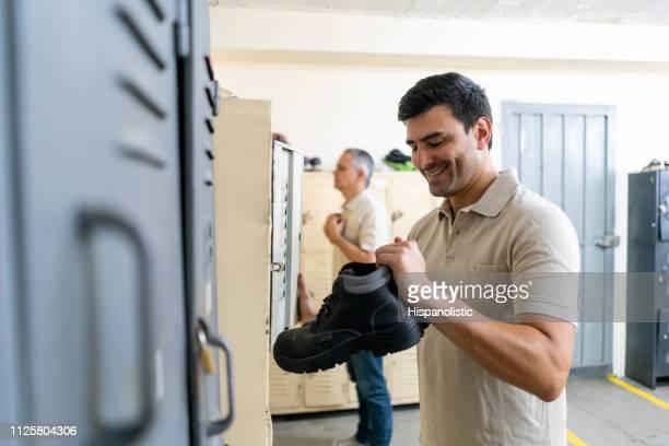 fröhliche lateinamerikanischen arbeiterin immer bereit, bei der fabrik lächelnd arbeiten - umkleideraum stock-fotos und bilder