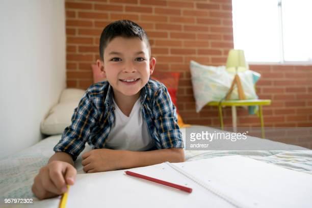 Vrolijke Latijns-Amerikaanse jongen liggen op zijn bed kijken camera glimlachen terwijl u tekent op zijn laptop