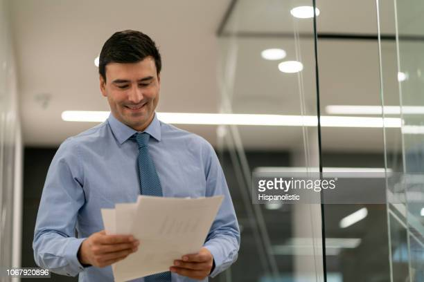 Cheerful latin american businessman at the office walking through corridor and looking at documents