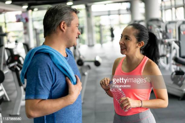Cheerful latin american couple at the gym taking a break after working out talking