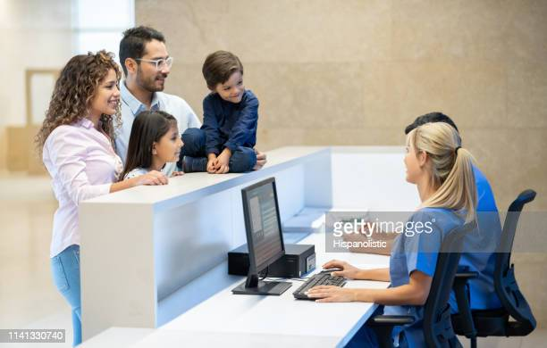 cheerful latin american family registering for a doctor's appointment at a medical center all smiling - medical receptionist uniforms stock pictures, royalty-free photos & images
