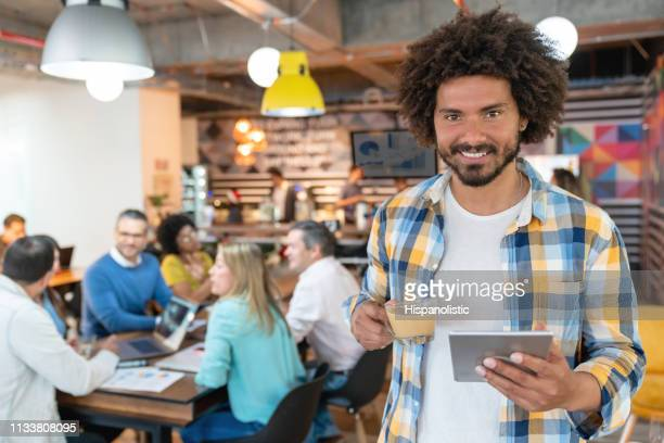 Cheerful latin american man at a coworking office holding a tablet and latte while smiling at camera