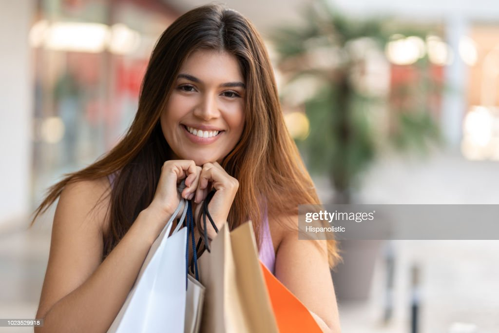 Cheerful latin american woman holding bags close to her while looking at camera smiling : Stock Photo