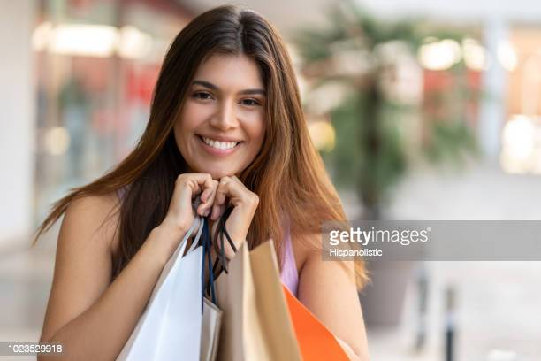 Cheerful latin american woman holding bags close to her while looking at camera smiling