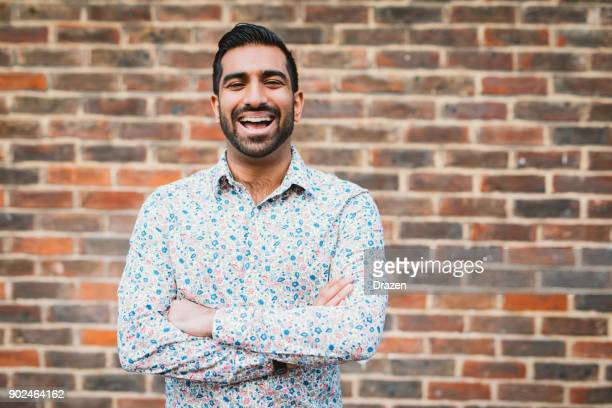 cheerful laughing indian man in casual shirt near the brick wall - handsome muscle men stock pictures, royalty-free photos & images