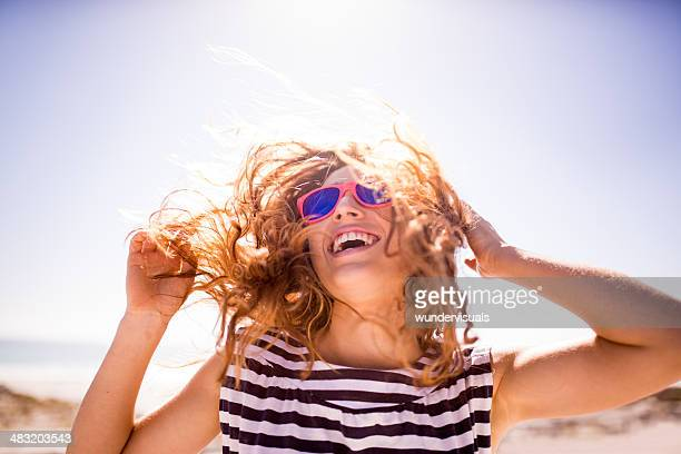 cheerful laughing woman on the beach - zonlicht stockfoto's en -beelden