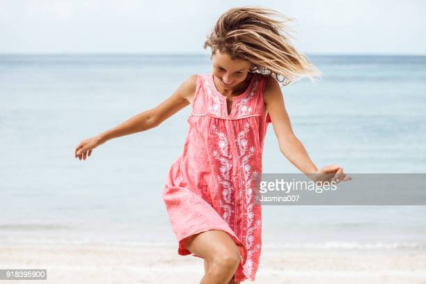 cheerful laughing woman on the beach - pink dress stock photos and pictures