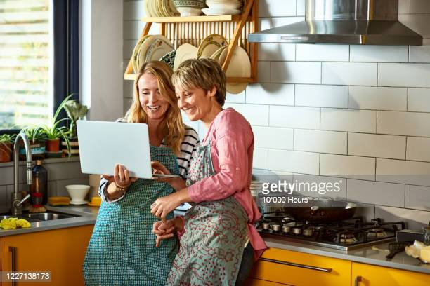 cheerful lesbian couple using laptop together in kitchen - computer stock pictures, royalty-free photos & images