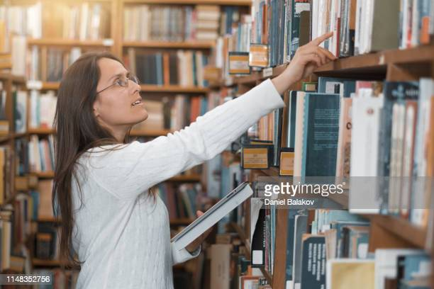 cheerful librarian. are books part of your life? be a librarian. - linguistics stock pictures, royalty-free photos & images