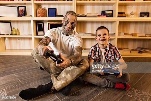 Alegre niño pequeño y su padre jugando juegos de vídeo.