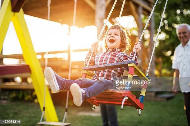 Cheerful little boy enjoying on a swing at sunset.