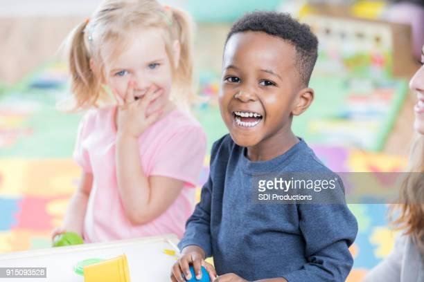 vrolijke kleine jongen genieten van kleuterschool - peuter stockfoto's en -beelden