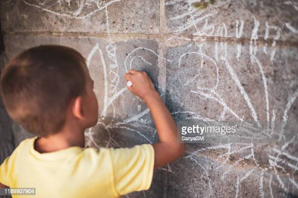 cheerful little boy having fun painting wall - chalk wall stock pictures, royalty-free photos & images