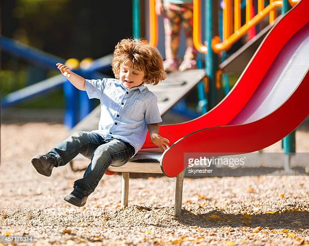 Cheerful little boy having fun while sliding outdoors.