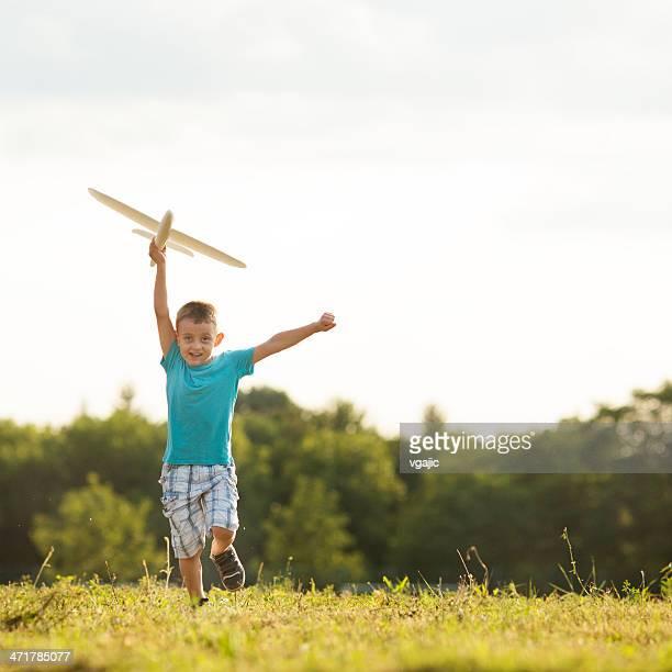 Alegre Little Boy divertir-se com o avião de brinquedo ao ar livre.