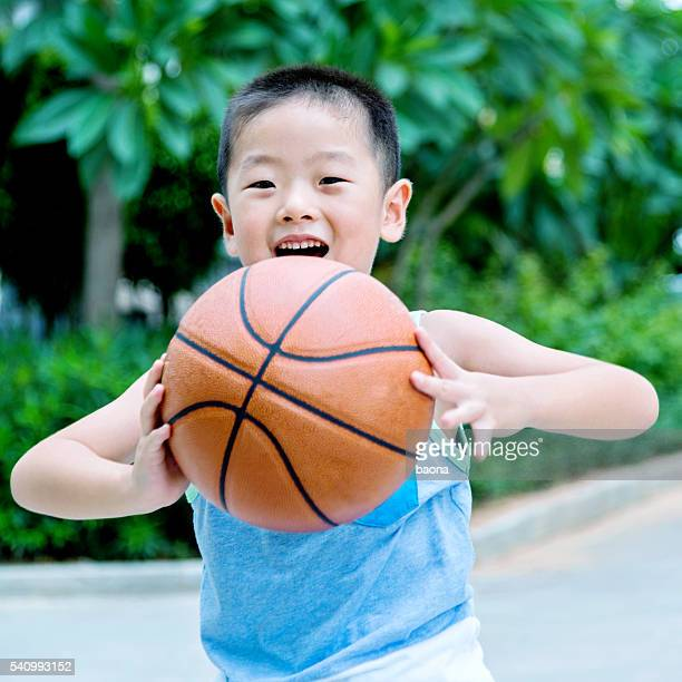 Cheerful little boy holding a basketball