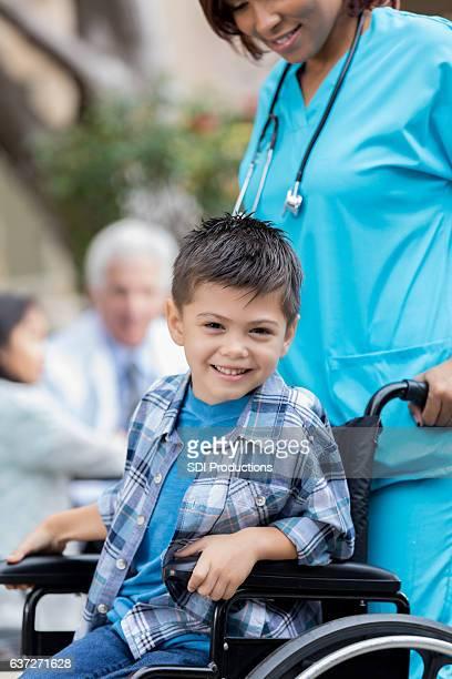 Cheerful little boy in wheelchair
