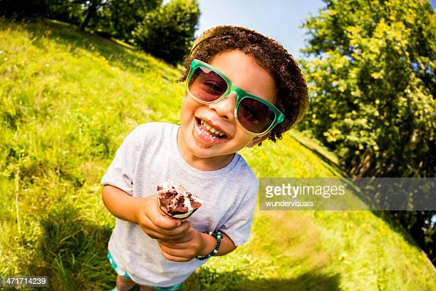 Cheerful little boy licking ice cream on a sunny day