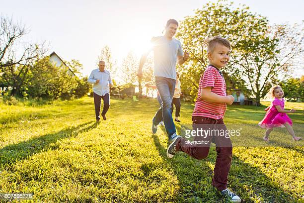 Cheerful little boy running in nature with his family.