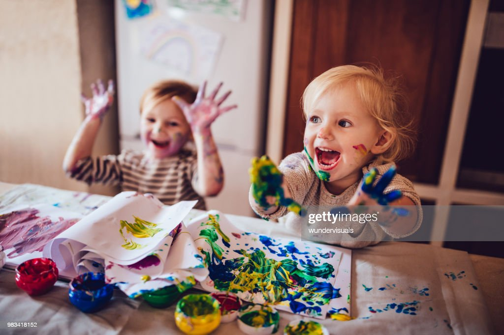 Cheerful little children having fun doing finger painting : Stock Photo