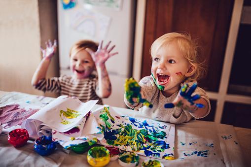 Cheerful little children having fun doing finger painting 983418152