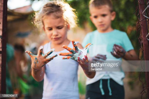 cheerful little children with colorful paint on hands - 4 girls finger painting stock pictures, royalty-free photos & images