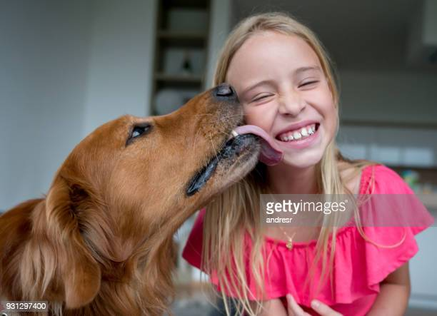 cheerful little girl and her pet licking her cheek looking very happy - licking stock pictures, royalty-free photos & images