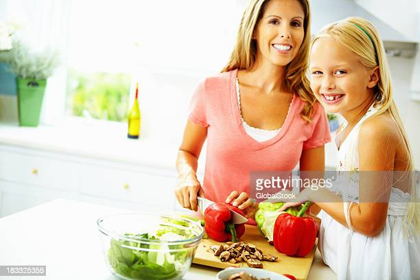 Cheerful little girl helping mother prepare food in the kitchen