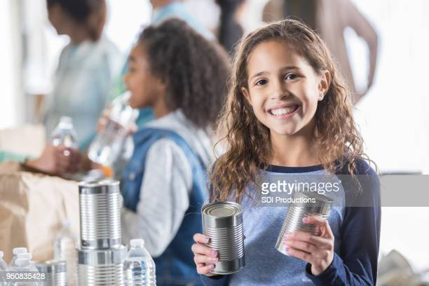 cheerful little girl helps sort cans of food at food bank - food drive stock pictures, royalty-free photos & images