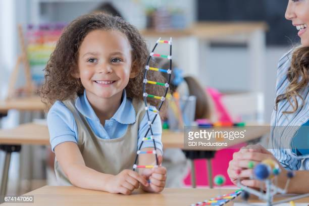 Cheerful little girl in science class