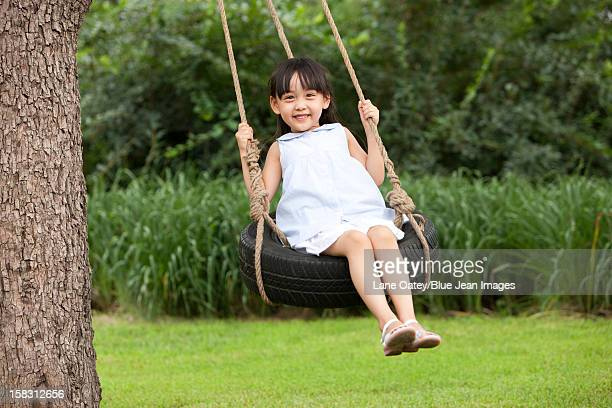 Cheerful little girl playing on a swing