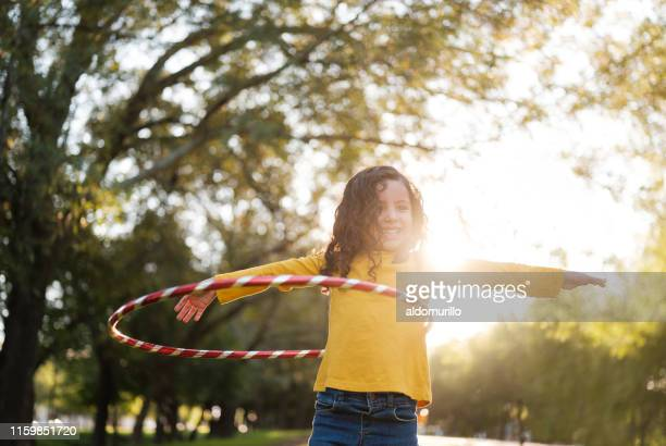cheerful little girl playing with a hula hoop - medium shot stock pictures, royalty-free photos & images