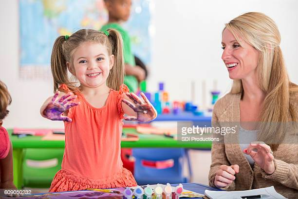 Cheerful little girl shows off her painted hands