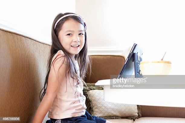 Cheerful little girl sitting at kitchen table with iPad