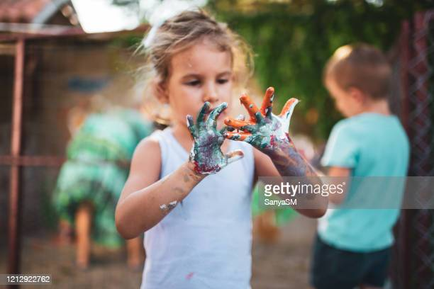 cheerful little girl with colorful paint on her hands - 4 girls finger painting stock pictures, royalty-free photos & images