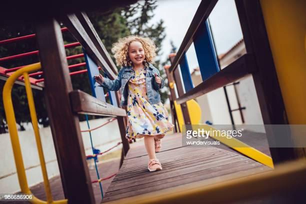 遊び場で遊んで巻き毛を持つ陽気な少女 - ジャングルジム ストックフォトと画像
