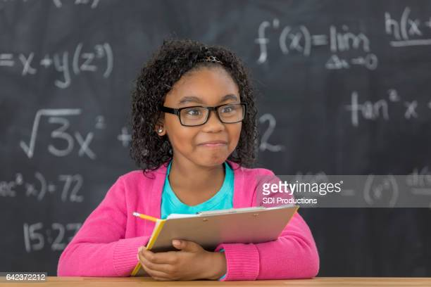 Cheerful little girl works on math assignment