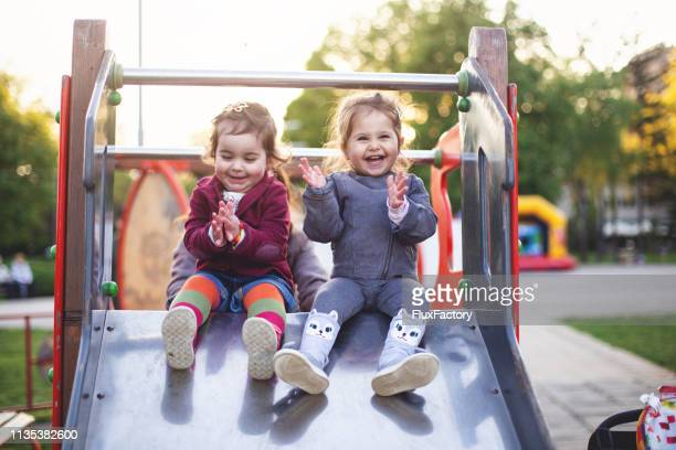 cheerful little girls sitting on a slide at the playground - playing stock pictures, royalty-free photos & images