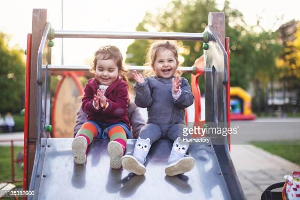 vrolijke kleine meisjes zittend op een glijbaan in de speeltuin - playing stockfoto's en -beelden