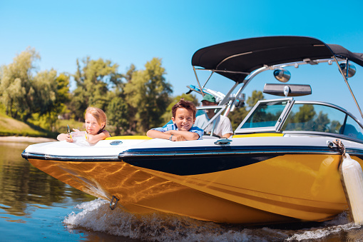 Cheerful little siblings enjoying view from boat bow 993481846