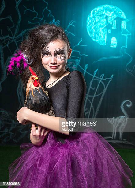 Cheerful little witch with rooster