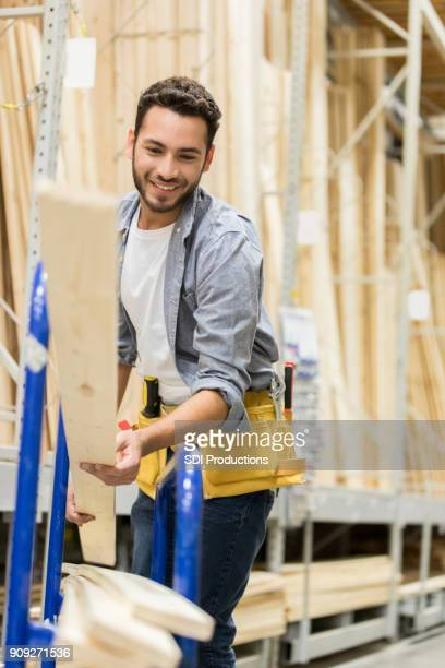 Cheerful lumber yard worker loads planks on a dolly