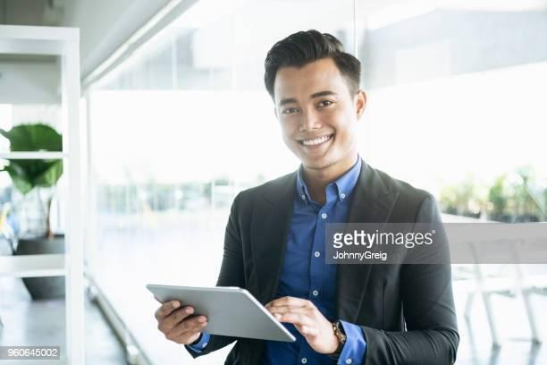 hombre de negocios malasio alegre con tableta digital - malasia fotografías e imágenes de stock