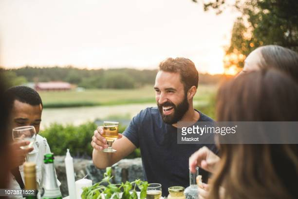 cheerful male and female friends enjoying drink dinner in backyard during sunset - india summer fotografías e imágenes de stock